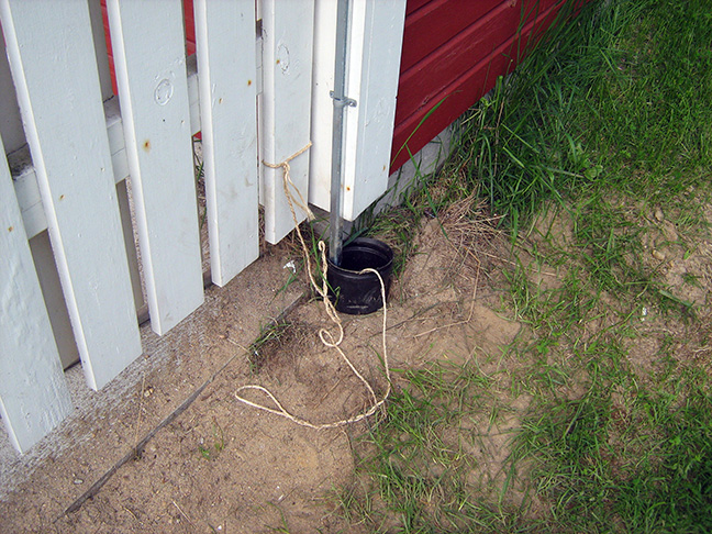 Talojen väliin asennettiin putki, josta kaapeli vedettiin narulla. Kotitalouden osuus alkaa siistillä suojakourulla.